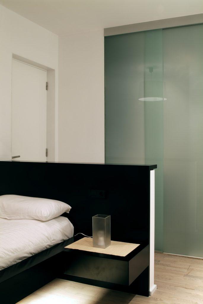 Diseño interior de piso en Galicia. Cama habitación con baño al fondo