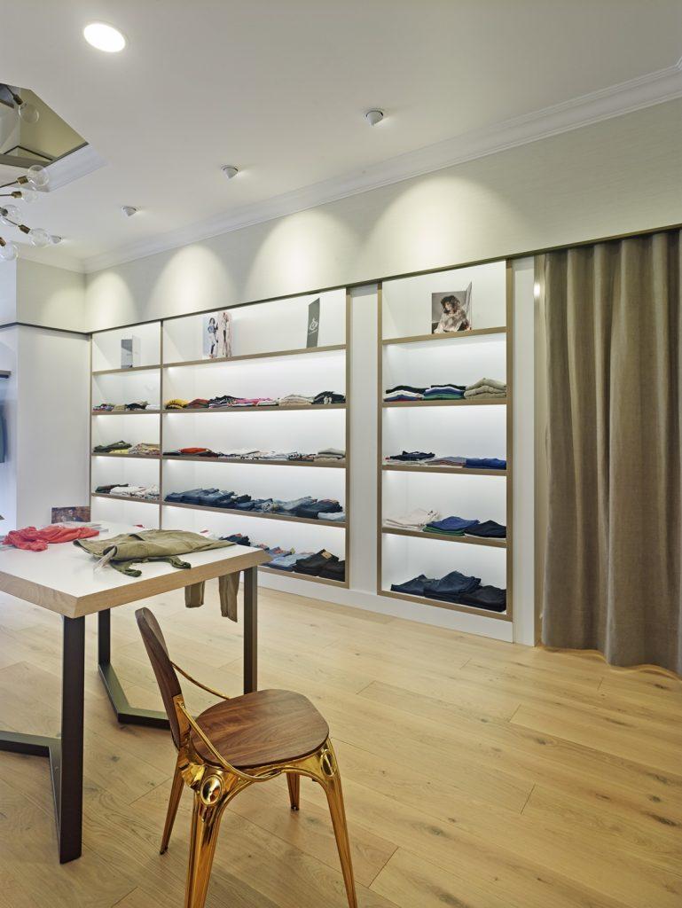 Vista lateral de la tienda, exposición y probadores en diseño interior de tienda de moda de mujer Jonathans